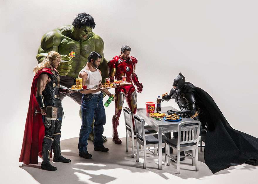 Batman is taking up most of a canteen table, Woverine, Hulk, Iron Man and Thor look on holding lunch trays