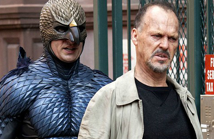 Michael Keaton is followed down the street by a main his height dressed as as a bird-like superhero