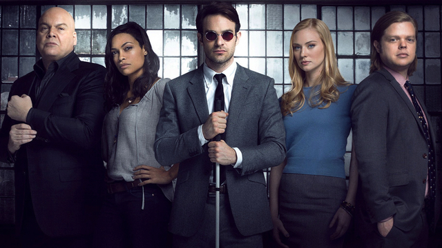 In front of a warehouse window, the cast line up of Daredavil stands with Charlie Cox, in the centre wearing dark glasses and holding his cane