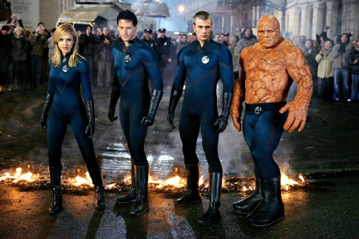Sue Storm, Reed Richards, Johnny Storm and the Thing stand in a line in their uniforms, in action poses