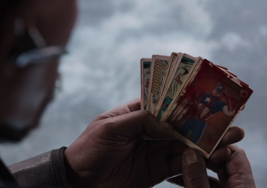 Blood smeared Captain America trading Cards fan out in Steve Roger's hands.